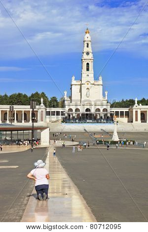 FATIMA, SPAIN - SEPTEMBER 29, 2008: The grand memorial and religious complex in small Portuguese town of Fatima. A woman in hat on his knees crawling on specially laid track to temple