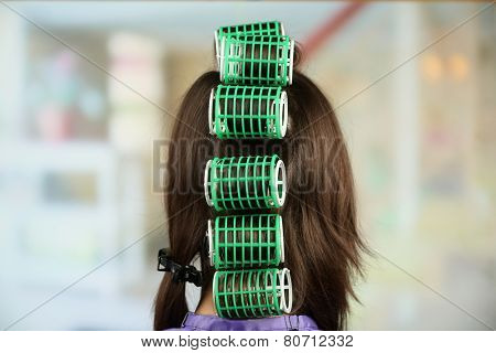 Long female hair during hair dressing with curler, close-up, on light background