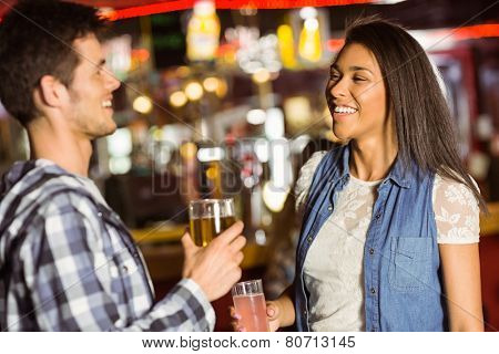 Smiling friends drinking beer and mixed drink in a bar