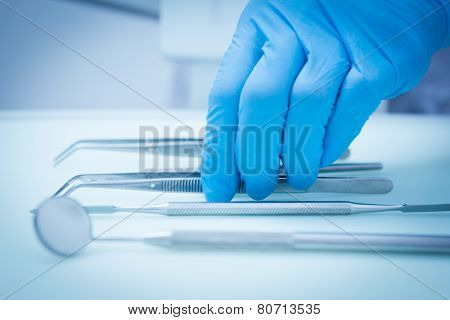 Close up of gloved hand picking dental tools