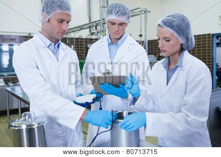 Man writing on clipboard while colleagues testing product in the factory