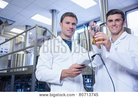 Men testing product and smiling at the camera in the factory