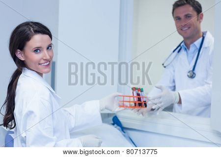Smiling biologists with blood sample looking at camera in hospital