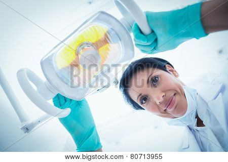 Low angle portrait of female dentist adjusting light