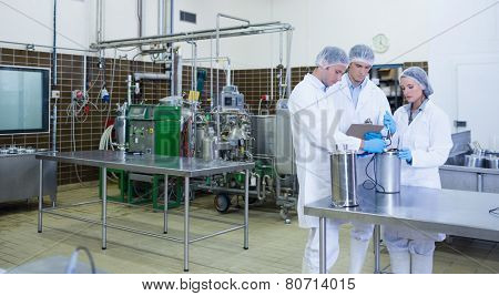 Man writing on his clipboard results of the experience in the factory