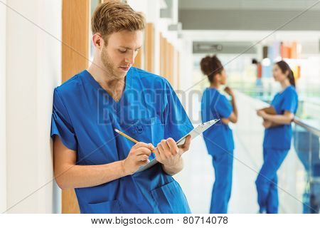 Medical student taking notes in hallway at the university