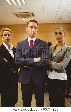 Three unsmiling lawyers looking at camera crossed arms in the court room