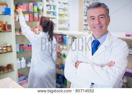 Pharmacist looking at camera with student behind him in the pharmacy