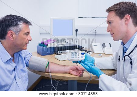 Doctor talking to his patient about his blood pressure at the hospital