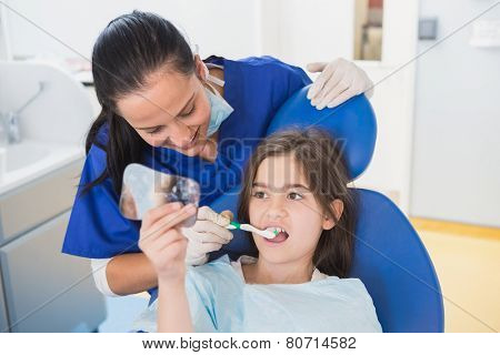 Pediatric dentist brushing teeth to her young patient in dental clinic