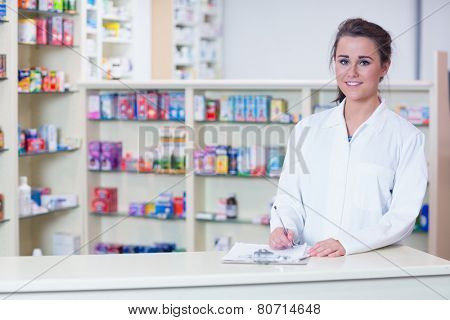 Smiling trainee in lab coat writing a prescription in the pharmacy