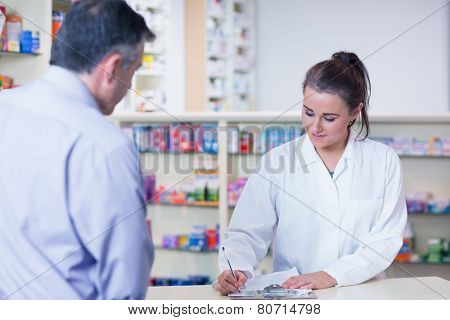 Trainee writing prescription in front of a customer in the pharmacy