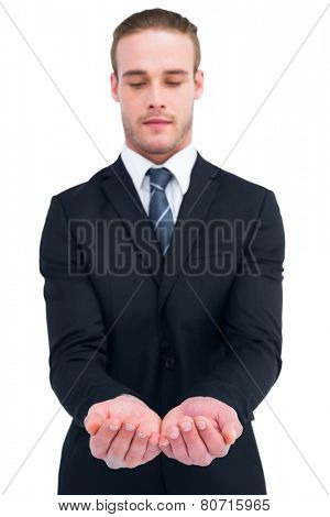 Concentrated businessman holding out his hands on white background