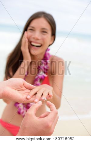 Marriage proposal casual couple beach wedding concept. Man proposing to girlfriend during holiday travel. Young lovers in love.