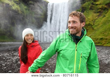 Happy couple holding hands by waterfall outdoors in front of Skogafoss on Iceland. Couple visiting famous tourist attractions and landmarks in Icelandic nature landscape on Golden Circle.