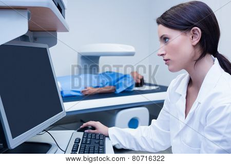 Doctor looking her computer while proceeding a radiography in hospital