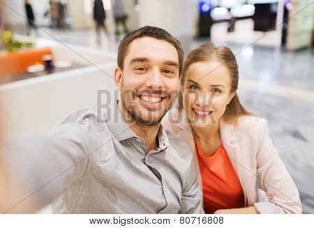 technology, photographing, and people concept - happy couple taking selfie with smartphone or camera in mall