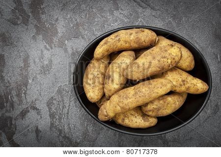 Unwashed raw fingerling or kipfler potatoes in a black dish over dark slate background.
