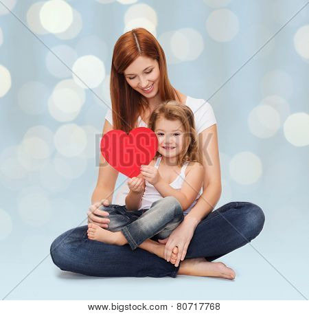 childhood, parenting, people and love concept - happy mother with adorable little girl holding red heart over holidays lights background