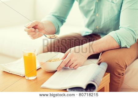 home, rest, news, breakfast and people concept - close up of man reading magazine and eating breakfast at home