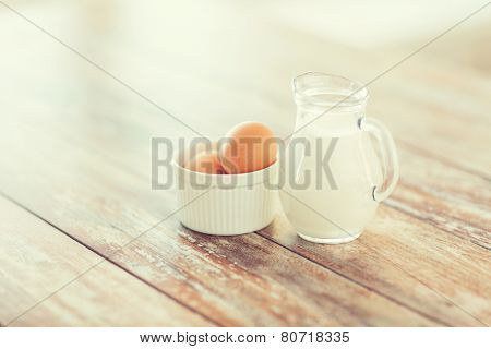 cooking and food concept - close up of jugful of milk and eggs in a bowl