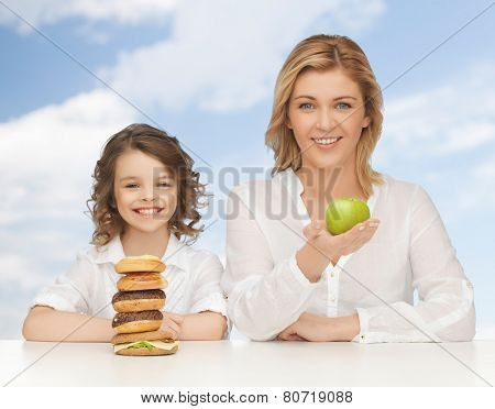 people, healthy lifestyle, family and unhealthy food concept - happy mother and daughter eating different food over blue sky background