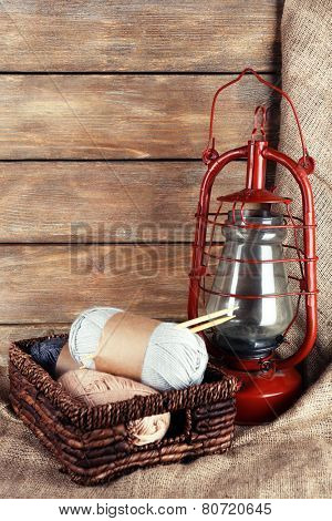Kerosene lamp with yarn and needles for knitting in wicker basket on wooden planks background