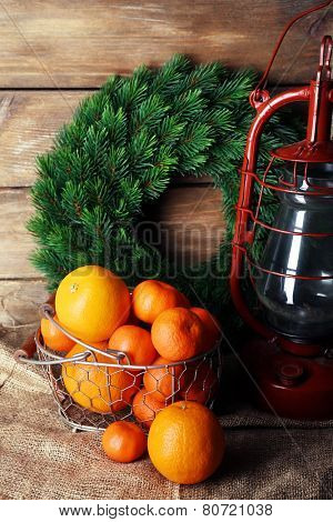 Kerosene lamp with wreath and oranges in wicker basket on wooden planks background
