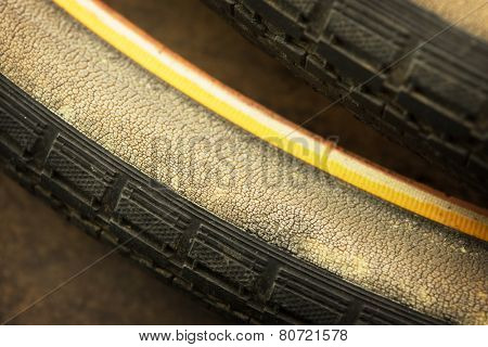 old dry, cracked and weathered bicycle tire.  deteriorating rubber.