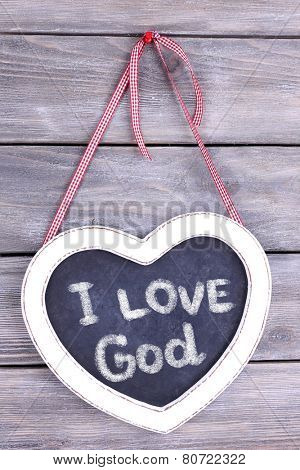 Heart shaped chalkboard and I love God text on wooden background