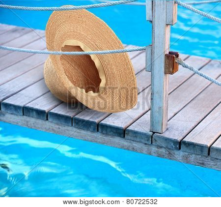 Summer hat on wooden bridge