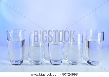 Glasses of water on table and colorful background