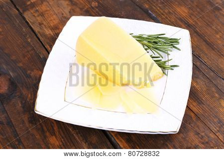 Parmesan cheese with sprig of rosemary on plate on wooden table background
