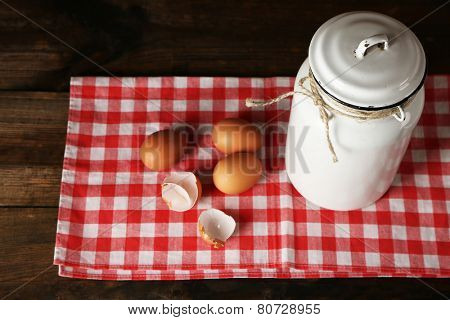 Milk can with eggs and eggshell on napkin on rustic wooden table background