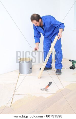 Worker in blue overalls applies glue to floorboard with spatula in white room