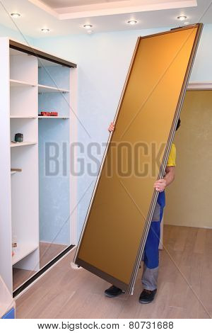 Worker holding door for sliding wardrobe in room with blue walls