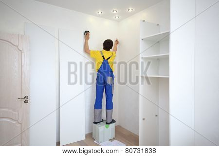 Man makes a mark on the wall to install a corner sliding wardrobe