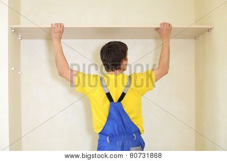 Worker fixes a shelf in the wall for the sliding wardrobe