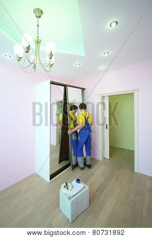 Young worker setting mirror door for sliding wardrobe in room with pink walls