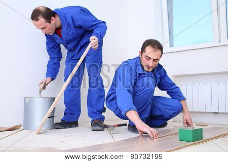 Two workers apply glue to the board with a spatula and put them on the floor