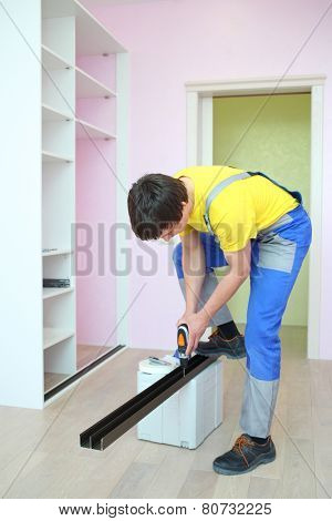 Worker installing guide rails for sliding wardrobe in room with pink walls