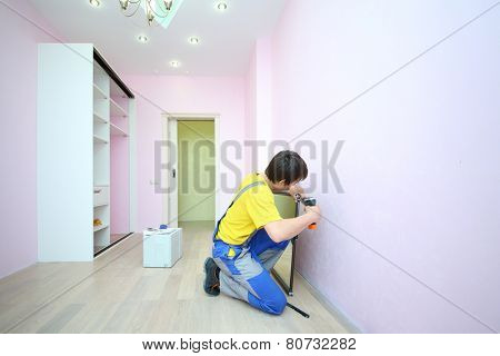 Man installing mirror door for sliding wardrobe in room with pink walls