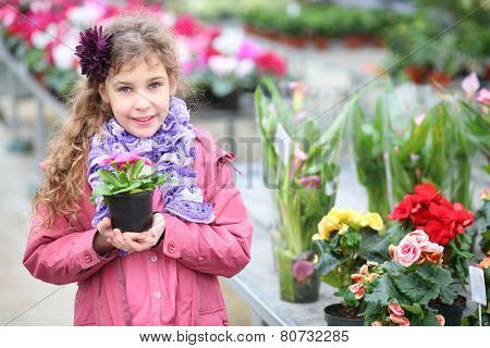 Smiling girl in a pink jacket holding flower pot in the hothouse