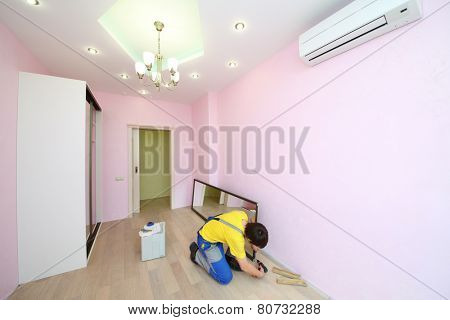 Worker setting mirror door for sliding wardrobe in room with pink walls
