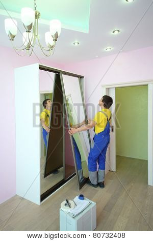 Young man setting mirror door for sliding wardrobe in room with pink walls