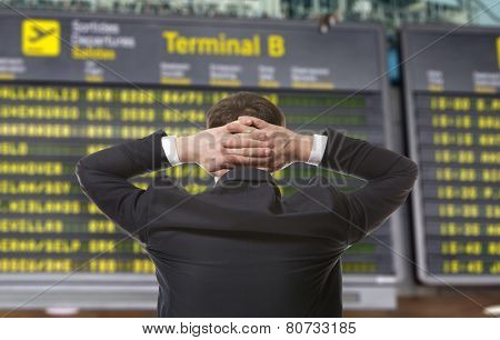 Businessman on a background of departure board at airport