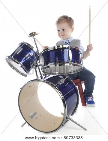 An adorable preschooler playing on a drum set.  On a white background.