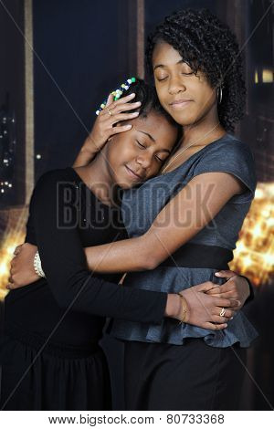 Beautiful African American sisters lovingly embracing each other before nighttime windows and white Christmas lights.