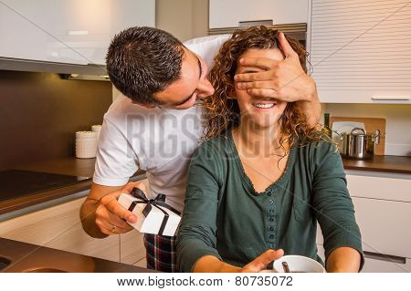 Man with gift box closing his girlfriend eyes for a surprise