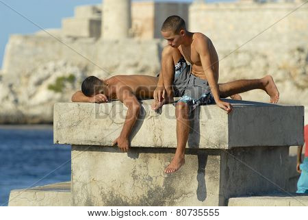 Young men sunbathe at the Malecon seawall, Havana, Cuba.
